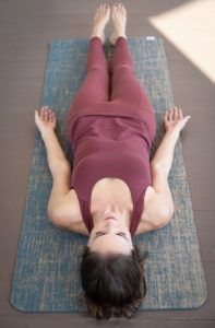nicole schoolfield in corpse pose yoga pose