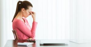 Woman with head down at table, 5 stages of stress.
