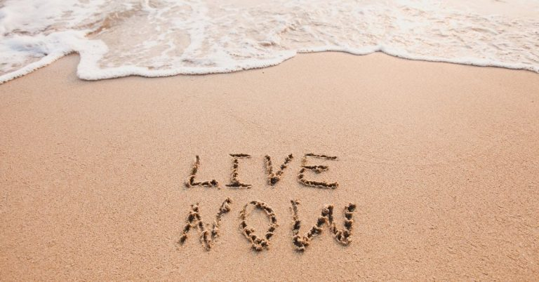 Live now drawn in sand on beach. How to practice mindfulness in daily life.