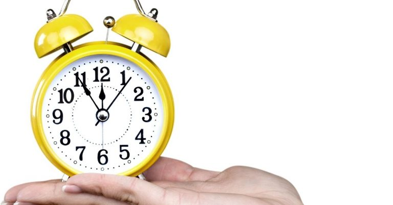 Person holding a yellow alarm clock. This post discusses the Pomodoro Technique pros and cons.