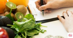 Person writing diet plan next to healthy foods. This post is about creating a hormonal imbalance diet plan.